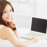 Young smiling asian woman  with laptop